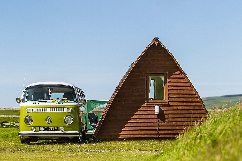 VW Green campervan parked next to wooden Wigwam